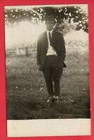 RPPC YOUNG MAN IN SUIT AND HAT OUTSIDE IN FRONT OF A FIELD  REAL PHOTO POSTCARD