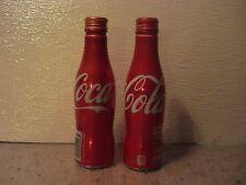 2 empty aluminum Coke bottles
