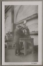1920's era Postcard - Man working in a workshop working with a manual press
