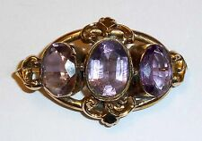 A VICTORIAN GOLD TONE BROOCH SET WITH AMETHYSTS
