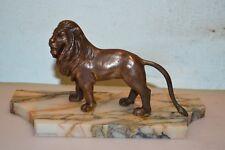 statue d'un lion en bronze sur socle en marbre
