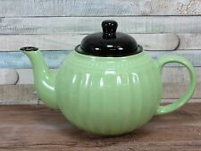 Green ceramic teapot with black lid and ribbed design afternoon tea