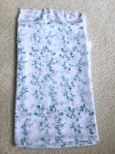 Semi-sheer white chiffon apparel fabric with teal blue botanical floral pattern.