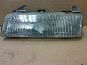 87' - 90' Chevrolet Beretta  LH headlight and mounting bracket  OEM