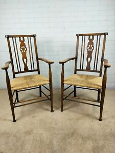 A Pair of Victorian Arts and Crafts Movement Open Arm Chairs with Rush Seats