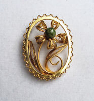 Vintage gold-tone filigree flower brooch with green stone center