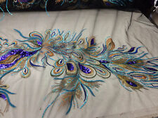 Turquoise peacock feathers on a black mesh lace embroider.45x50 inches. Sold by