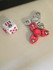 two red and silver figet spinners and one pink and white figet cube