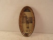 antique oval metal frame, photo of young lady in fur coat, 3 by 6 in.,  No. 1084