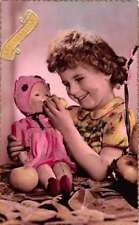 Little Girl Feeding Fruit to Baby Doll Tinted Real Photo Postcard J73928