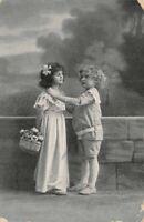 CPA - Photo d'Art - Jeune garçon et une fillette portant un panier de fleurs
