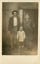 RPPC Postcard Very Sad Men with Dead Eyes and a Barefoot Boy Child With a Hammer