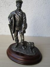MERLIN FINE ARTS LTD BPC  PEWTER HUNTER WITH DOG ON CARVED WOODEN PLINTH.