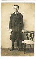 RPPC Young MAn in Suit with Pants Rolled Up, Victorian Chair Real Photo Postcard
