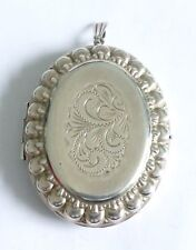 A LARGE VINTAGE SILVER OPENING LOCKET WITH AN ENGRAVED DESIGN & SCALLOPED EDGE