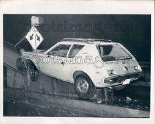 AMC Gremlin Auto Wreck on Bridge Abutment Press Photo
