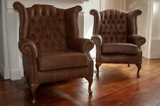 A pair of Queen Anne wing back chairs and footstool in vintage brown leather