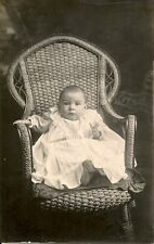 Postcard Photo of a Baby sitting in a wicker chair. No Photographer.