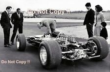 Graham Hill checking over his new Lotus 49 1967 Photograph