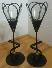 A PAIR OF CONE SHAPE CANDLE HOLDERS NESTED ON A BLACK ALUMINUM RACK