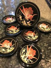 Six decorated black lacquer coasters in a matching round box.