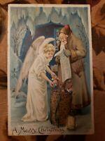 1909 Brown Robe Santa with List Basket of Toys & Angel Merry Christmas postcard