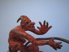An ancient, bronze figure. Damn, the devil, Satan.