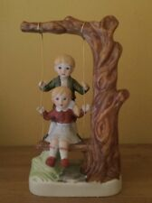 Vintage boy & girl on a Tree swing