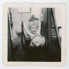 Joyful childhood moment blond Little girl on swing set. Vintage snapshot photo