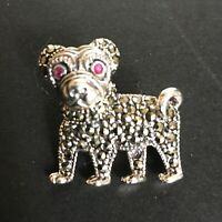 A sterling silver figural brooch in the form of a dog.