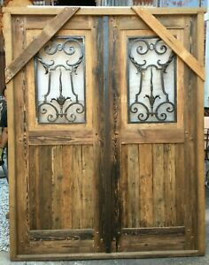 Double wooden Spanish door with hand forged wrought iron insert