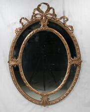 Oval gold gilt Venetian mirror with ribbon pediment and scroll design. Lot 111