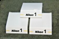 Three Nikon white display stands