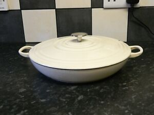 cast iron shallow casserole dish and lid in cream