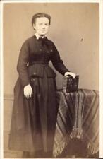 CDV anonyme femme debout tenant un album photo habillée en noir col blanc 1870