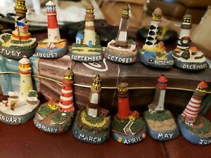 """Set of 12 mini Lighthouses.  One for each month of the year.  Resin & approx 2""""."""