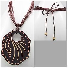 Cotton necklace with carved wood centerpiece depicting tribal patterns.