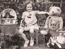 Altes Foto von Kind mit großem Teddy und Puppen von 1934