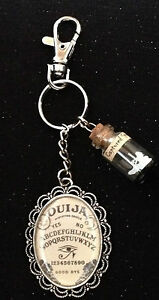 Novelty Ouija board with 'Captured Spirit' in a bottle. Keyring/ bag charm.