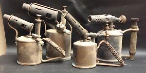 four antique brass blow-lamps
