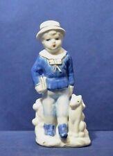 Boy in blue with dog figurine