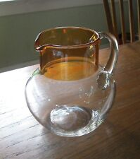 """Vtg. clear pitcher w/orange top. Just under 6"""" tall. Fat bottom. 3 1/4"""" across."""