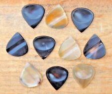 10 Buffalo Horn Guitar pick with hand carved groove on it and thumb impression