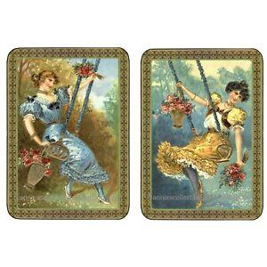 Pair of vintage style ladies on swings playing swap cards