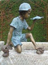 statue en bronze d un garçon avec une tortue , jet d eau , étang , fontaine .