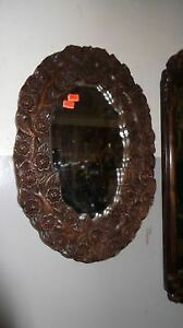 A vintage, oval , brown , floral framed wall mirror