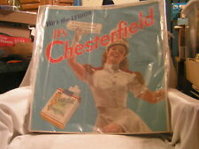 CHESTERFIELD SIGN WITH BETTY ATKINSON HOLDING A GREEN CARTON  OF CIGARETTES