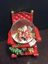 Palla di vetro con neve su sedia a dondolo. Scena natalizia con babbo natale