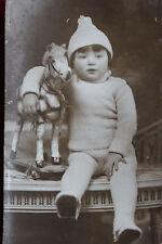 CPA Photographie ancienne bébé avec bonnet tenant son cheval à roulettes Jouet