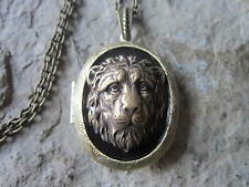 BRONZE SAD LION LOCKET ON BLACK BACKGROUND - AFRICA, LION HEAD, SAFARI